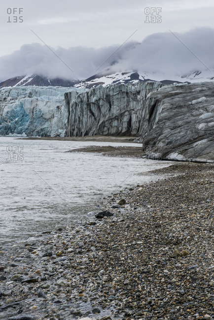 Gravel beach before a huge glacier in Hornsund, Svalbard