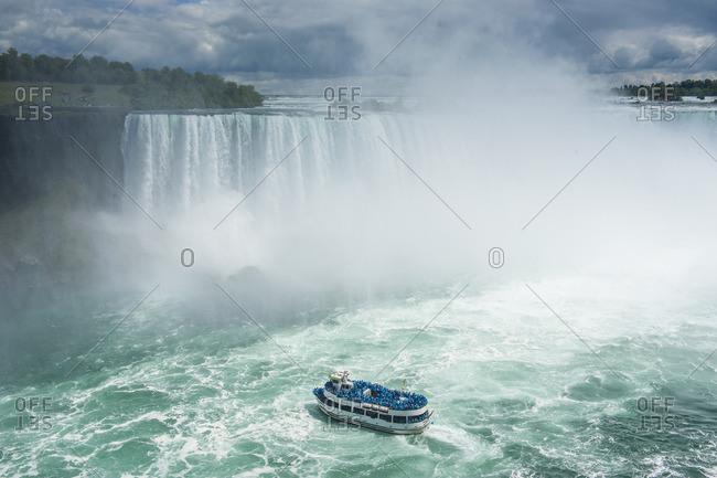 Tourist boat in the mist of the Horseshoe Falls (Canadian Falls), Niagara Falls, Ontario, Canada