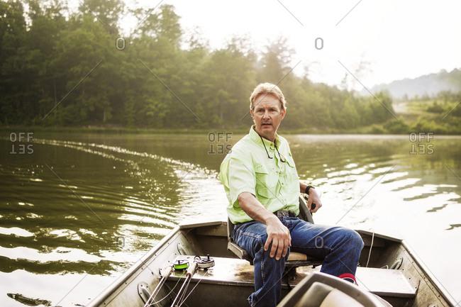 Man steering motor boat on lake