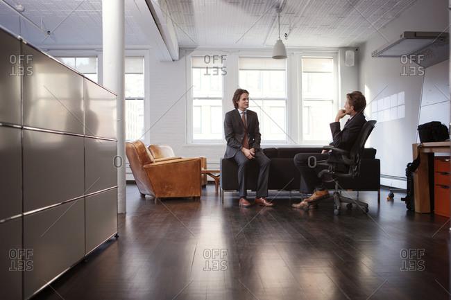 Two corporate men in office talking