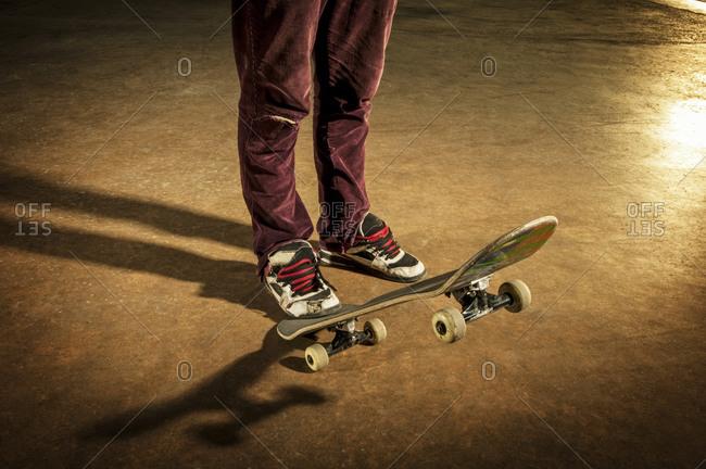 Skateboarder stepping on back of skateboard