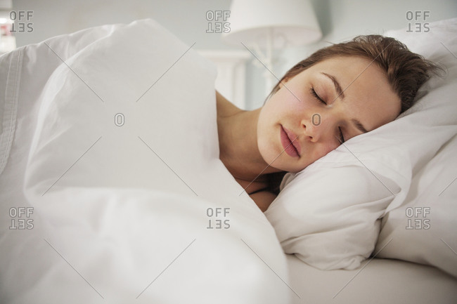 Portrait of woman asleep in cozy bed