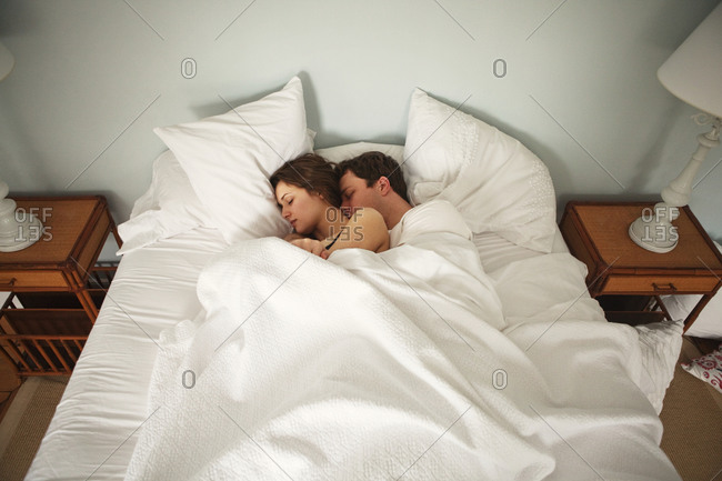 Couple Cuddling Asleep In Bed Stock Photo