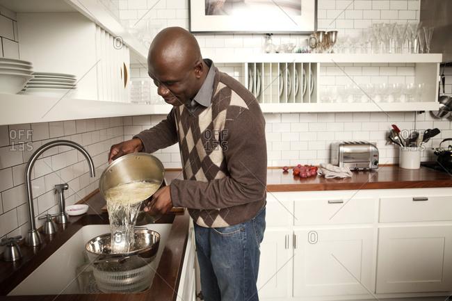 Man in kitchen straining pasta