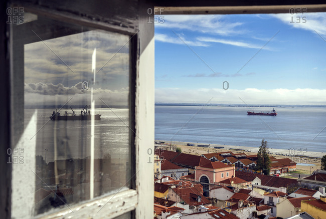View of Alfama neighborhood and ship on the river Tejo through open window