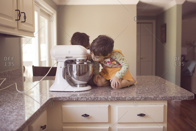 Two children watch a stand mixer