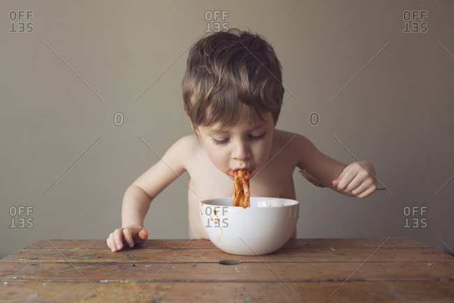 Young boy eating pasta