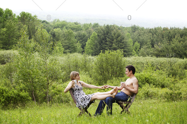 Romantic couple drinking coffee in front of a wooded view