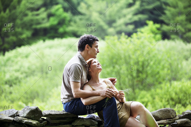 Romantic couple sitting outside on a rock wall
