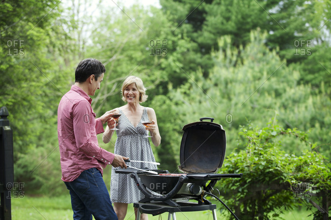Man and woman drinking wine while grilling