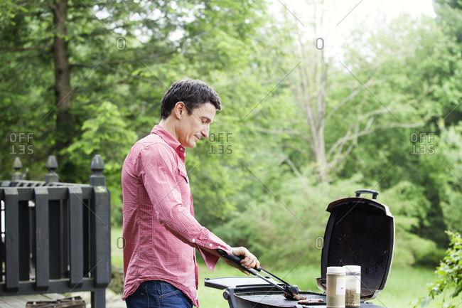Man preparing grilled food outside his home