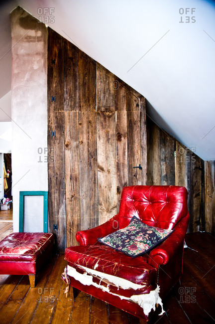 Red armchair with barn wood walls