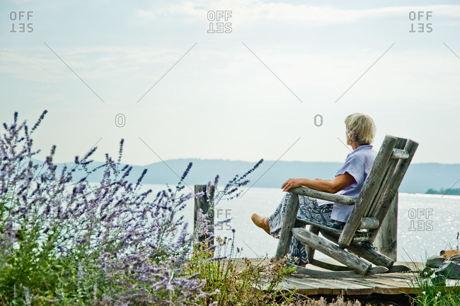 Piermont, NY, USA - August 6, 2010: Joan Gussow sitting on a pier along the Hudson river
