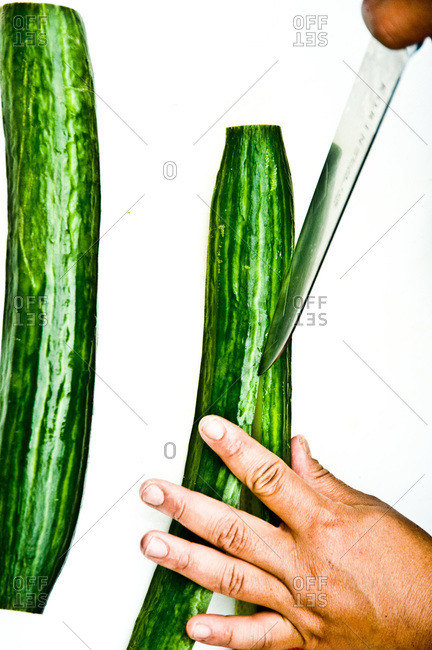 Person halving a Chinese cucumber