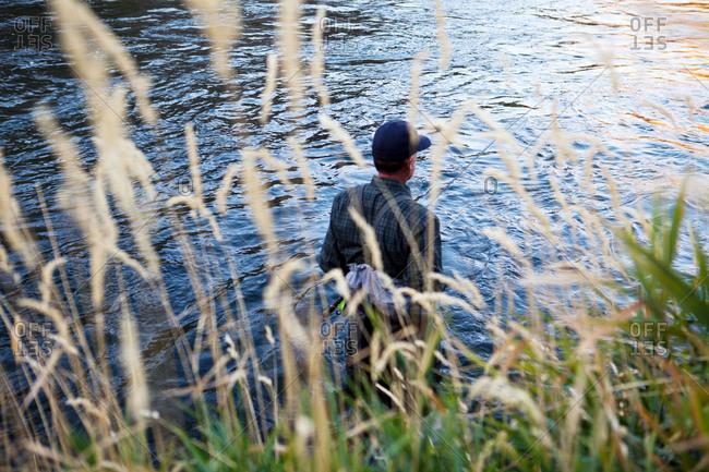 A fisherman wading near the shore