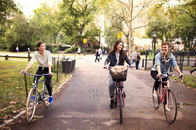 Hip young women riding bicycles in city park
