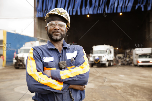 A worker stands in front of trucks at a recycling plant