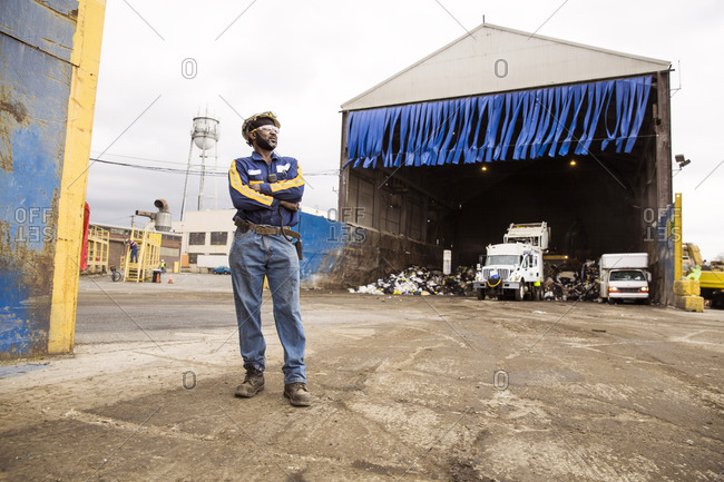 A worker stands outside at a recycling plant