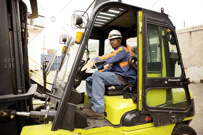 A worker operates a forklift at a recycling plant