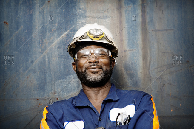An industrial worker at a recycling plant smiles