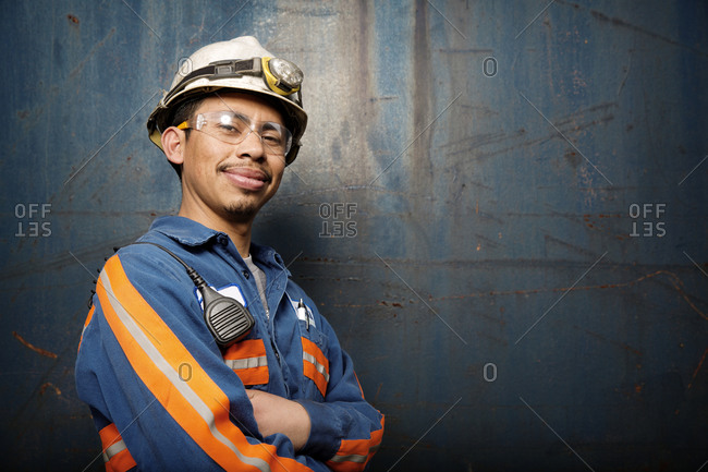 A worker at a recycling plant smiles