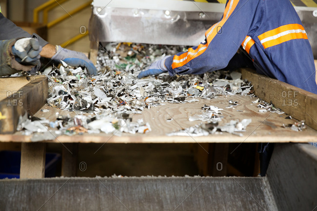 Industrial workers sort through recycled materials