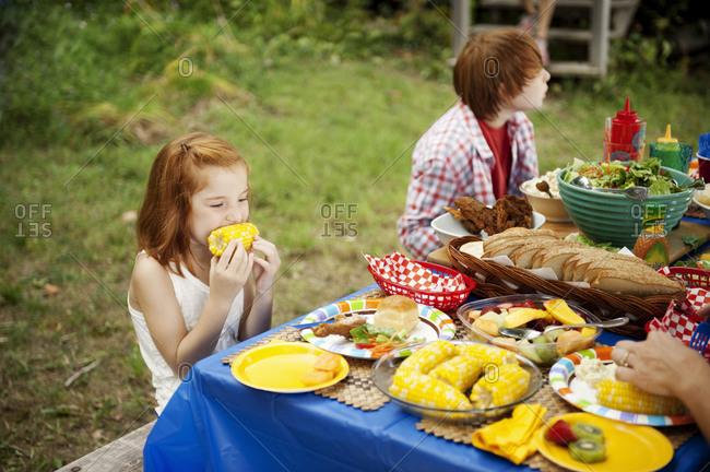 A young girl eats corn at a family picnic
