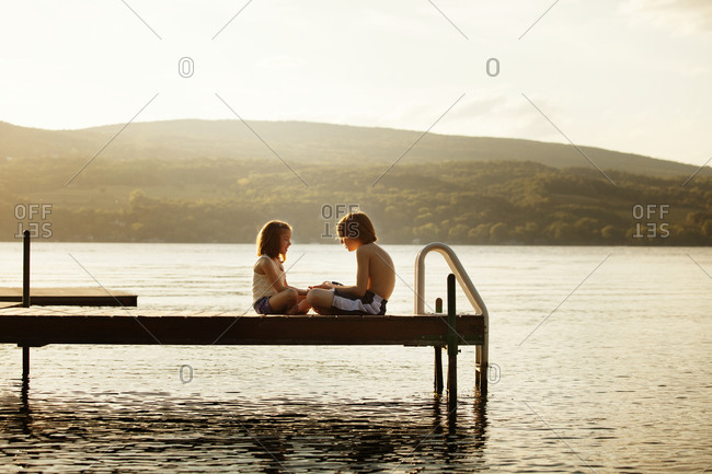 Siblings sit on a dock playing a hand slapping game