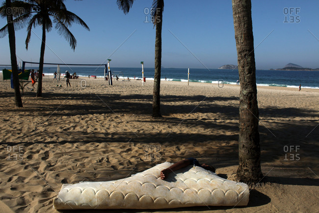 Man sleeping on an old mattress at Ipanema beach