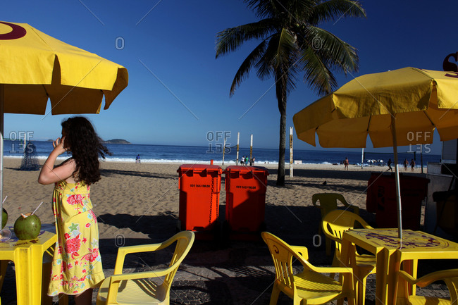 Young girl with a drink of fresh coconut water on Ipanema beach