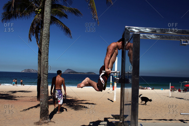 Men work out at a fitness workstations on the Copacabana beach
