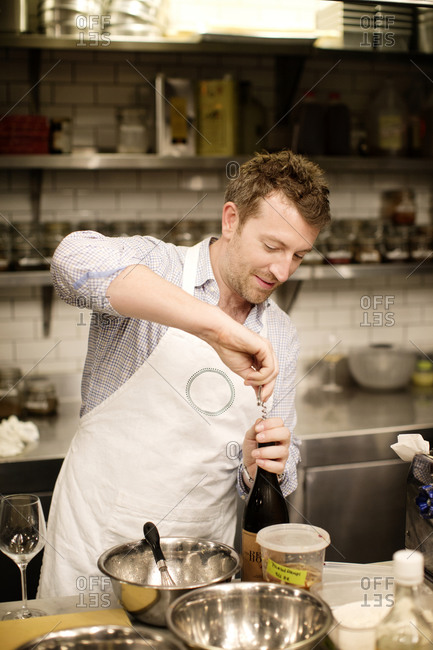 A student chef opens a bottle of wine in a kitchen