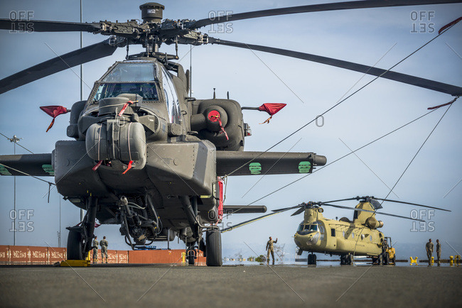 US Army Apache and Chinook Helicopters tied down and awaiting to be loaded aboard a ship