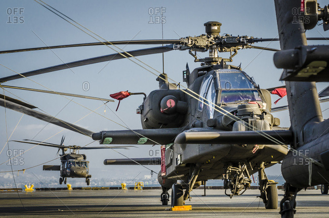 A US Army Blackhawk helicopter takes off at the Port of San Diego while Apache helicopters are tied down awaiting loading aboard a cargo ship