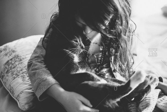 A little girl holds a cat