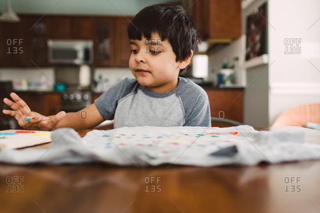 A little boy decorates a shirt