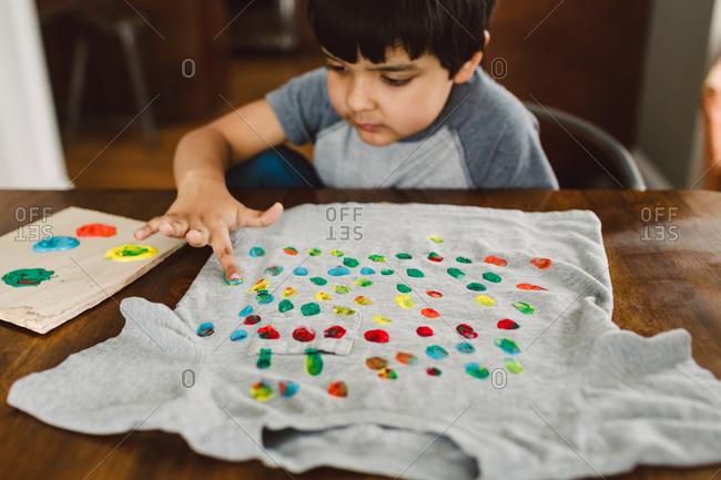 A little boy paints dots on a shirt