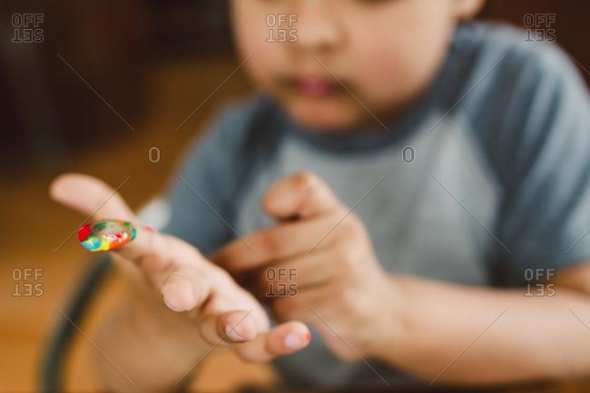 A little boy picks paint of his hand