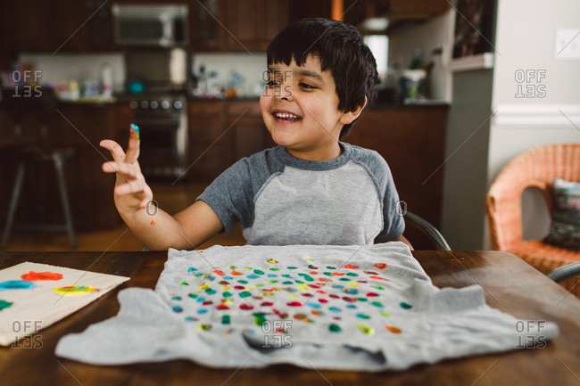 A boy examines his paint-covered hand