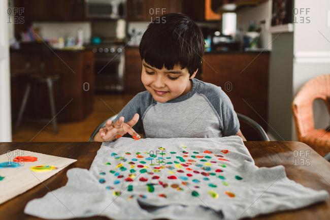 A boy smiles as he decorates a shirt