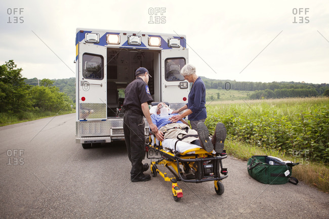 EMT with patient on stretcher on rural road