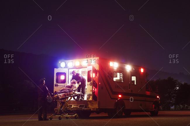 EMTs loading patient onto ambulance at night