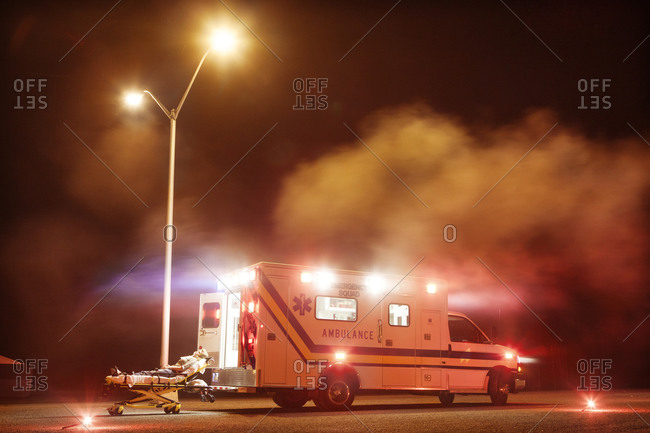 Ambulance surrounded by fog at night