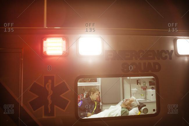 EMT assisting elderly patient inside ambulance at night