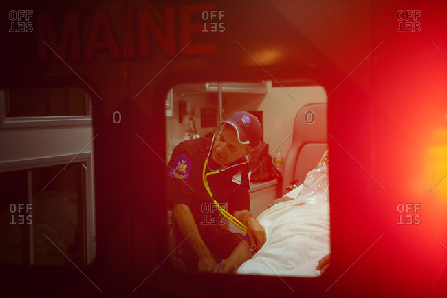 EMT checking heart rate of injured person in ambulance
