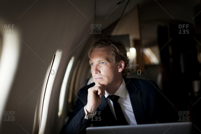 Businessman looking out of window of a private jet