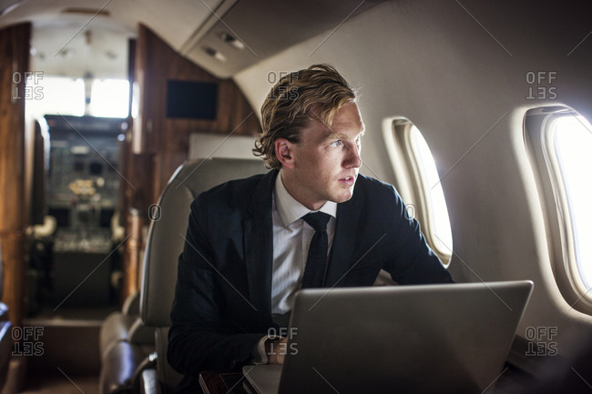 Businessman with laptop on private jet