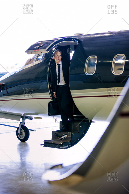 Businessman stepping out of private jet