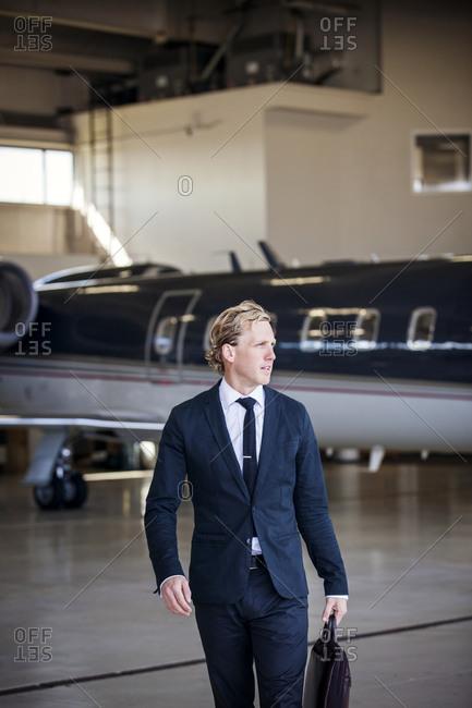 Businessman walking in hangar by private jet