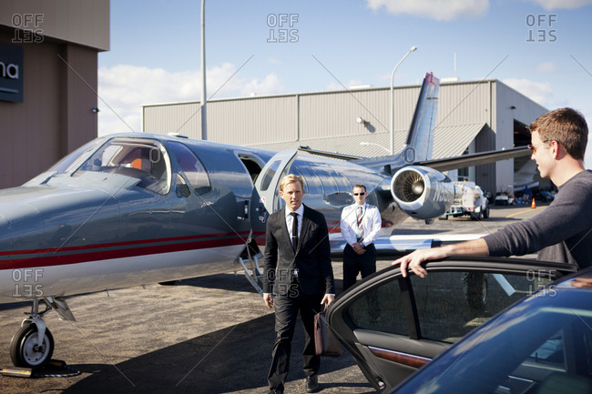 Businessman leaving private jet and entering a limousine